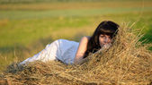 Beautiful woman on the haystack. — Stock Photo