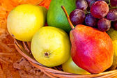 Yellow, red and green pears with red grapes in woven baskets — Stock Photo