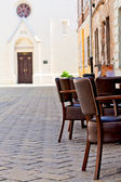Chairs on the narrow street in old town — Stock Photo