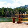 Table with benches on the pier mountain lake - Stock Photo