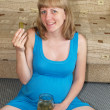 Stock Photo: The pregnant woman eats a pickle, sitting on a floor