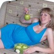 Stock Photo: The pregnant woman holds a green apple
