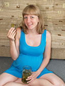 The pregnant woman eats a pickle, sitting on a floor — Stock Photo