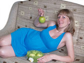 The pregnant woman holds a green apple — Stock Photo