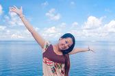 Aziatisch meisje heffen wapens op zee — Stockfoto