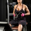 Asian woman working out on rower in gym — Stockfoto
