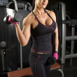 Stock Photo: Asian woman working out with weights in gym