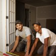 Multi ethnic team working on flooring - Stock Photo