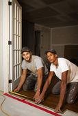 Multi ethnic team working on flooring — Stock Photo