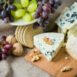 Cheese still life with red grapes, walnuts and crackers - Стоковая фотография