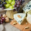 Cheese still life with red grapes, walnuts and crackers - Stockfoto