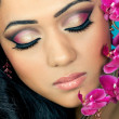 Beautiful young woman's face with orchid flowers - Stock Photo