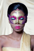Beautiful young woman wearing a golden carnival mask — Stock Photo