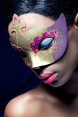 Beauty portrait of a young black woman wearing mask — Stock Photo
