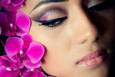 Closeup shot of a beautiful woman's face with orchid flowers — Stock Photo