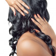 Beautiful woman with hands on her curly hair - Stock Photo