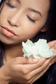 Beautiful young woman holding a white flower near her face — Stock Photo