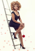 Young beautiful woman on a ladder holding a Christmas ball — Stock Photo