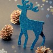 Christmas decorations: reindeer figure and golden pine cones — Stock Photo