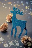 Christmas decorations: reindeer figure and golden pine cones — Stock Photo