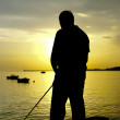 Silhouette of a fisherman — Stock Photo