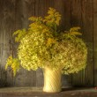 Retro style still life of dried flowers in vase against worn woo — Foto Stock