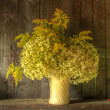 Retro style still life of dried flowers in vase against worn woo — 图库照片