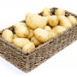Fresh new potatoes in rustic basket isolated on white background - Stock Photo