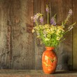 Stock Photo: Retro style still life of dried flowers in vase against worn woo