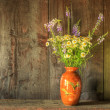 Retro style still life of dried flowers in vase against worn woo - Stock Photo