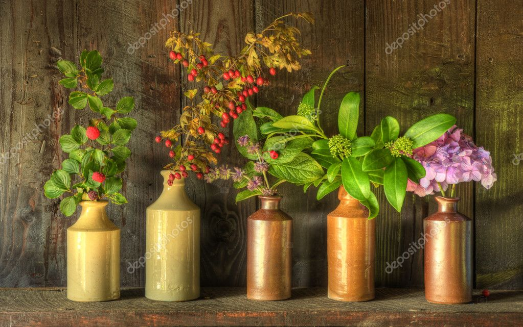 Still life image of dried flowers in rustic vase against weathered wooden background  Stock Photo #7025806