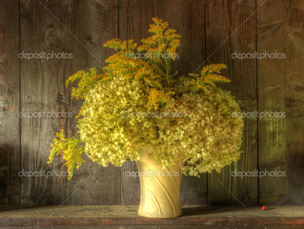 Still life image of dried flowers in rustic vase against weathered wooden background  Stock Photo #7025828