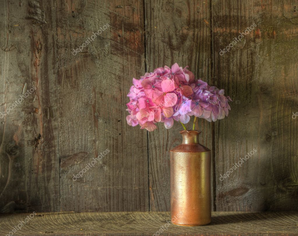 Still life image of dried flowers in rustic vase against weathered wooden background — Stock Photo #7025844