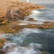 Постер, плакат: Stunning geological rock cliff formations with waves crashing in