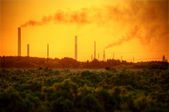 Industrial chimney stacks in natural landscape polluting the air — Stock Photo