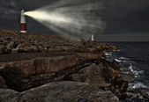 Victorian lighthouse on promontory of rocky cliffs with beam ali — Stock Photo