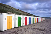 Row of colorful beach huts receding into distance on empty beach — Stock Photo
