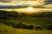 Stunning countryside landscape with sun lighting side of hills a — Stock Photo
