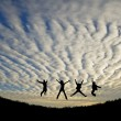 Постер, плакат: Silhhuette of four adults jumping for joy or achievement against
