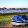 Stock Photo: Old rowing boat in low tide harbour landscape at sunset