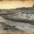 Stock Photo: Low tide harbour at sunset with nearby town in distance retro gr