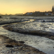 Stock Photo: Low tide harbour at sunset with nearby town in distance nad stre