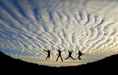 Silhhuette of four adults jumping for joy or achievement against — Stock Photo