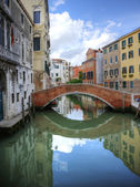 Beautiful reflections of bridge in canal in Venice Italy — Stock Photo