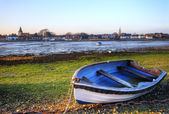 Old rowing boat in low tide harbour landscape at sunset — Stock Photo
