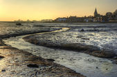 Low tide harbour at sunset with nearby town in distance nad stre — Stock Photo