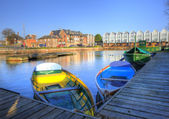 Bright colorful rowing boats in urban canal landscape — Stock Photo