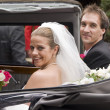 Stock Photo: Bride and groom arrive at reception in vintage wedding car