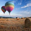 Royalty-Free Stock Photo: Hot air balloons over hay bales sunset landscape