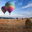 Hot air balloons over hay bales sunset landscape — Stock Photo #7127568